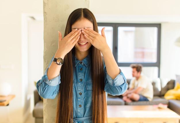 Jonge mooie aziatische vrouw die en gelukkig glimlacht, ogen met beide handen bedekt en op ongelooflijke verrassing wacht