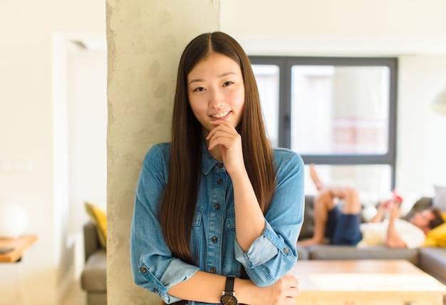 Jonge mooie aziatische vrouw die gelukkig kijkt en met hand op kin glimlacht, zich afvraagt of een vraag stelt, opties vergelijkt