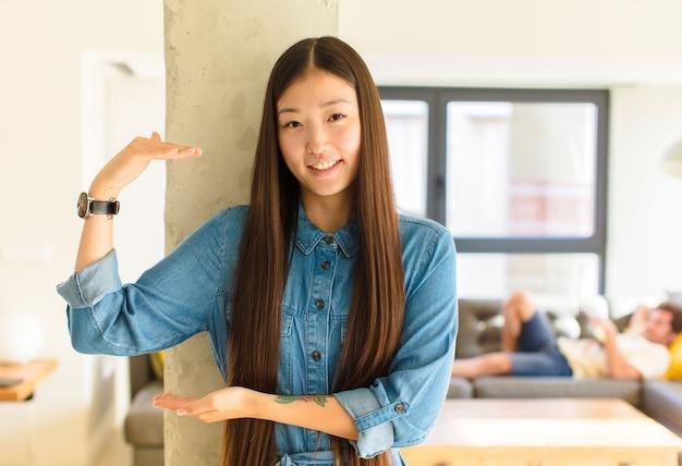 Jonge mooie aziatische vrouw die, gelukkig, positief en tevreden glimlacht voelt, voorwerp of concept op exemplaarruimte vasthoudt of toont