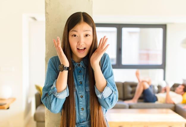 Jonge mooie aziatische vrouw die geschokt en opgewonden voelt, lacht, verbaasd en gelukkig is vanwege een onverwachte verrassing