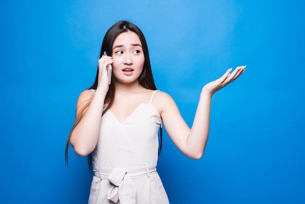 Jonge mooie aziatische vrouw die gesprek heeft die op smartphone spreekt die over blauwe muur wordt geïsoleerd