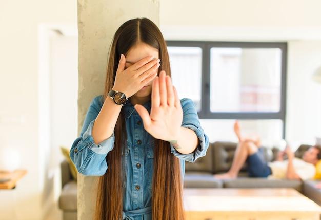 Jonge mooie aziatische vrouw die gezicht behandelt met hand en andere hand vooraan zet om camera tegen te houden
