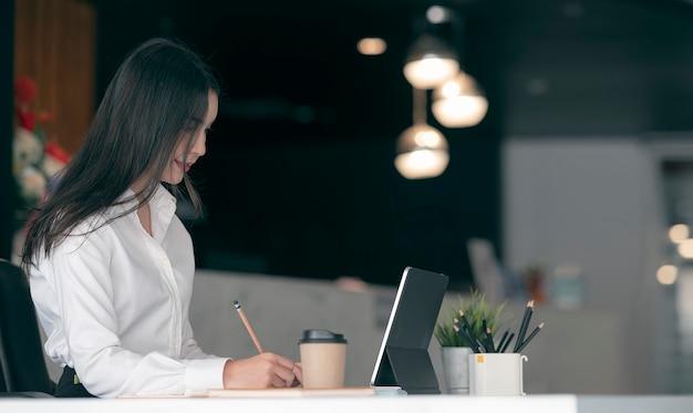 Jonge mooie aziatische vrouw die iets met potlood schrijft terwijl zij aan haar bureau in moderne bureauruimte zit.
