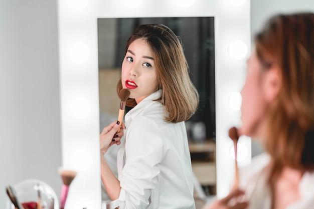 Jonge mooie aziatische vrouw die make-up in de buurt van spiegel