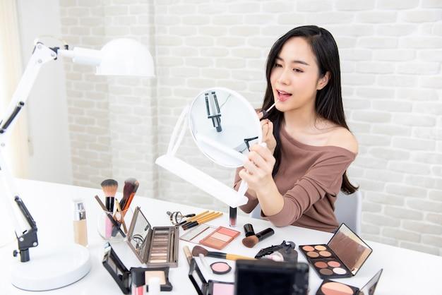 Jonge mooie aziatische vrouw die make-upleerprogramma doet