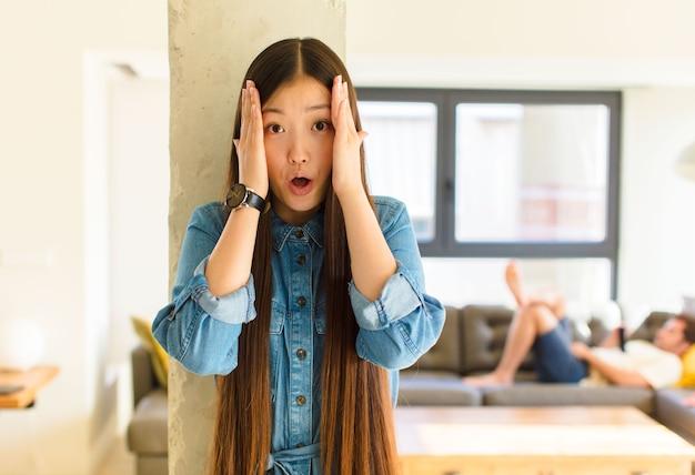 Jonge mooie aziatische vrouw die onaangenaam geschokt, bang of bezorgd kijkt, wijd open mond en beide oren bedekt met handen