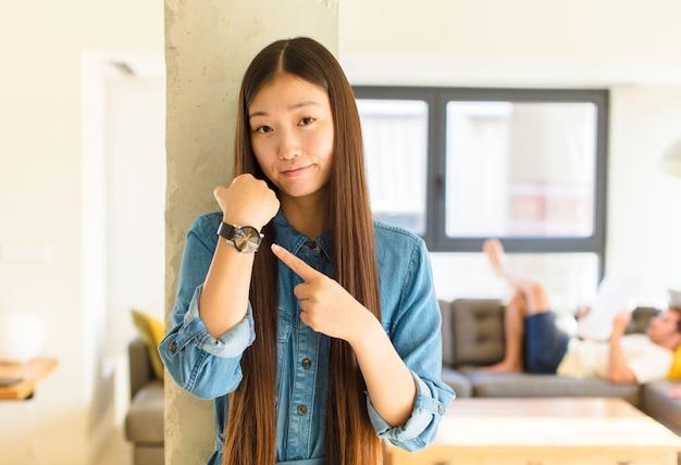 Jonge mooie aziatische vrouw die ongeduldig en boos kijkt, op horloge wijst, om stiptheid vraagt, wil op tijd zijn