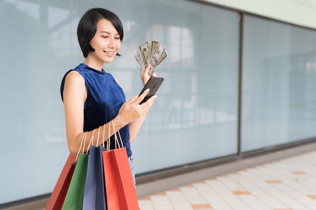 Jonge mooie aziatische vrouw die op haar mobiele telefoon met geld winkelt terwijl het houden van kleuren volledige het winkelen zakken in haar wapens met het glimlachen gezicht.
