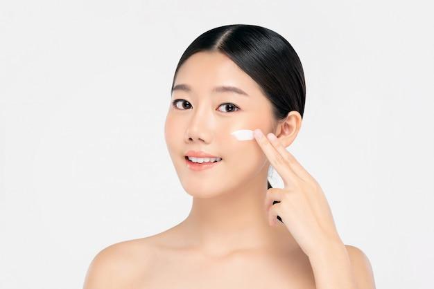 Jonge mooie aziatische vrouw die room toepast op gezicht