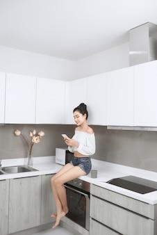 Jonge mooie aziatische vrouw die smartphone gebruikt en glimlacht terwijl ze in de keuken zit
