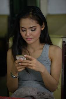 Jonge mooie aziatische vrouw die telefoon met behulp van bij de koffiewinkel