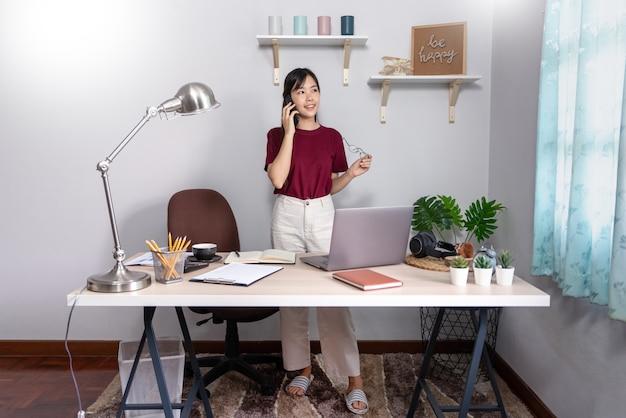 Jonge mooie aziatische vrouw die thuis werkt