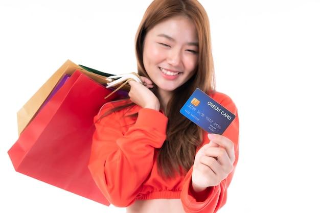 Jonge, mooie aziatische vrouw die veel boodschappentas vasthoudt en creditcard toont voor betaling winkelen geïsoleerd op een witte achtergrond - selectieve focus