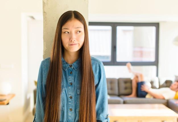 Jonge mooie aziatische vrouw die verbaasd en verward kijkt, zich afvraagt of probeert een probleem op te lossen of te denken