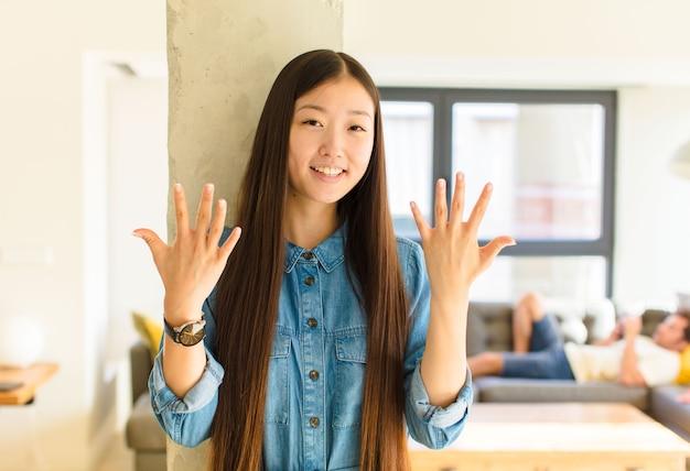 Jonge mooie aziatische vrouw die vriendelijk glimlacht kijkt, nummer tien of tiende met vooruit hand toont, aftellend