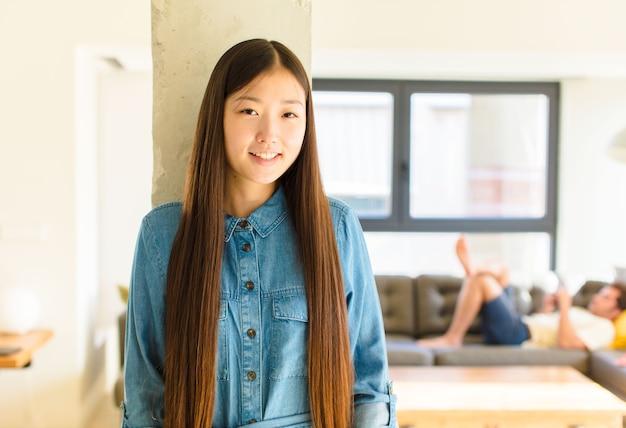 Jonge mooie aziatische vrouw die vrolijk en terloops glimlacht met een positieve, gelukkige, zelfverzekerde en ontspannen uitdrukking