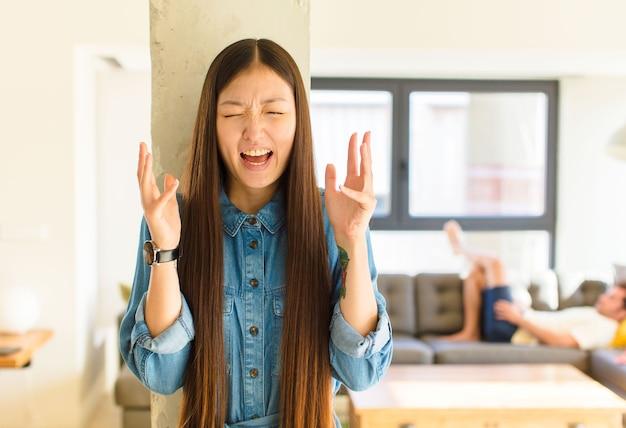 Jonge mooie aziatische vrouw die woedend schreeuwt, zich gestrest en geïrriteerd voelt met de handen in de lucht