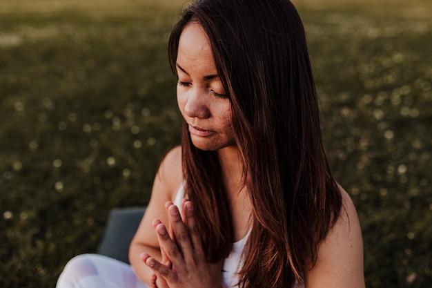 Jonge mooie aziatische vrouw die yoga in een park doet bij zonsondergang. yoga en gezonde levensstijl concept