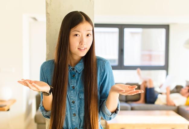 Jonge mooie aziatische vrouw die zich geen idee en verward voelt, niet zeker weet welke keuze of optie ze moet kiezen, zich afvragend