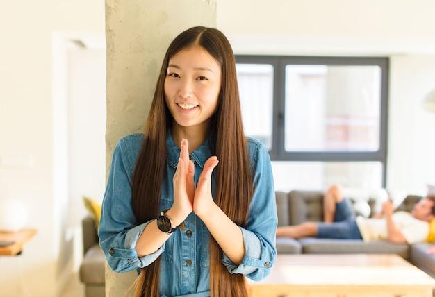 Jonge mooie aziatische vrouw die zich gelukkig en succesvol voelt, lacht en klapt in de handen, gefeliciteerd met een applaus