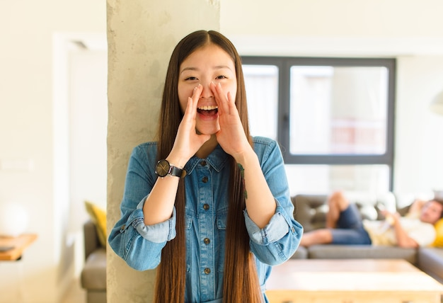 Jonge mooie aziatische vrouw die zich gelukkig, opgewonden en positief voelt, een grote schreeuw geeft met handen naast de mond, roept