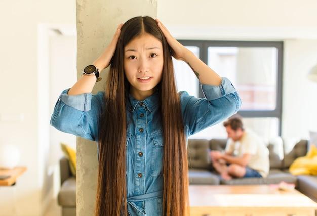 Jonge mooie aziatische vrouw die zich gestrest, bezorgd, angstig of bang voelt, met de handen op het hoofd, in paniek raakt bij vergissing