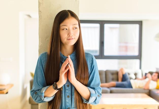 Jonge mooie aziatische vrouw die zich trots, ondeugend en arrogant voelt terwijl ze een slecht plan bedenkt of aan een truc denkt