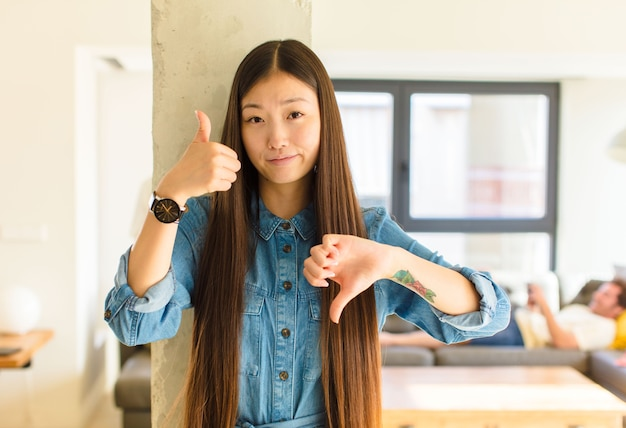 Jonge mooie aziatische vrouw die zich verward, geen idee en onzeker voelt en het goede en slechte in verschillende opties of keuzes weegt