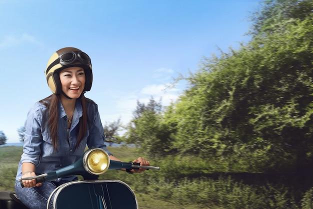 Jonge mooie aziatische vrouw die zijn autoped berijdt