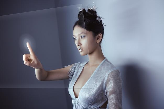 Jonge mooie aziatische vrouw digitaal hologramscherm aan te raken