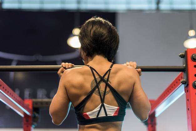 Jonge mooie aziatische vrouw doet pull-up op sportschool
