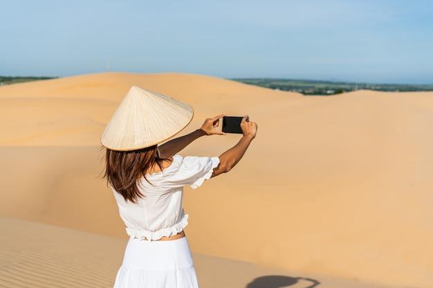 Jonge mooie aziatische vrouw geniet van het moment in de woestijn.