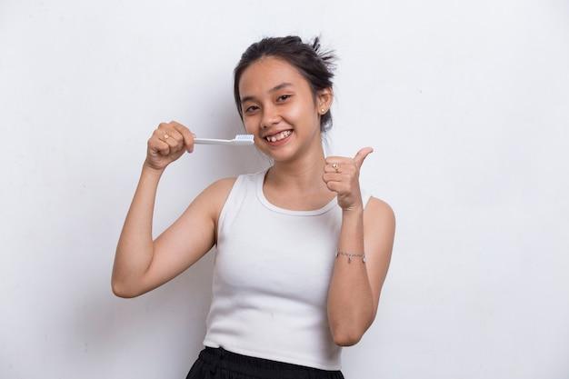 Jonge mooie aziatische vrouw haar tanden poetsen geïsoleerd op een witte achtergrond
