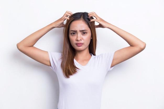 Jonge mooie aziatische vrouw hoofd krabben met de hand geïsoleerd op een witte achtergrond