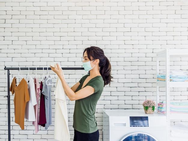 Jonge mooie aziatische vrouw, huisvrouw dragen casual doek en beschermend gezichtsmasker houden shirt, vuile vlek erop controleren na het wassen