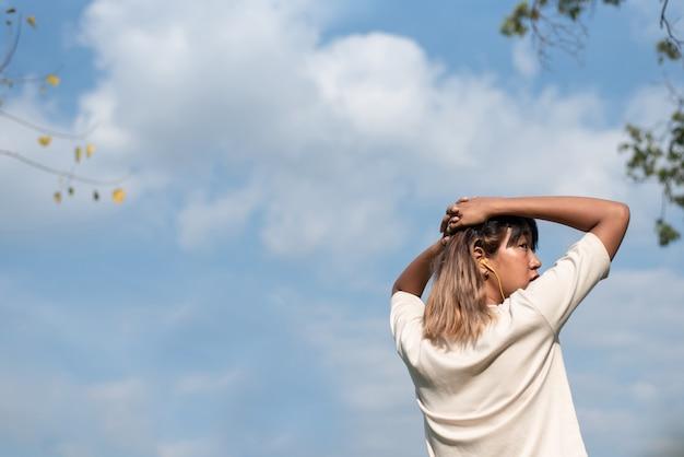 Jonge mooie aziatische vrouw in afkoelingspositie na het sporten in het park