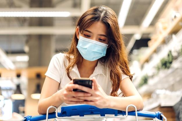 Jonge mooie aziatische vrouw in quarantaine voor coronavirus die chirurgische maskergezichtsbescherming draagt