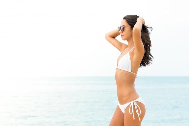 Jonge mooie aziatische vrouw in witte biniki op het strand in de zomer