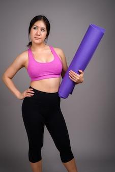 Jonge mooie aziatische vrouw klaar voor sportschool tegen grijze muur