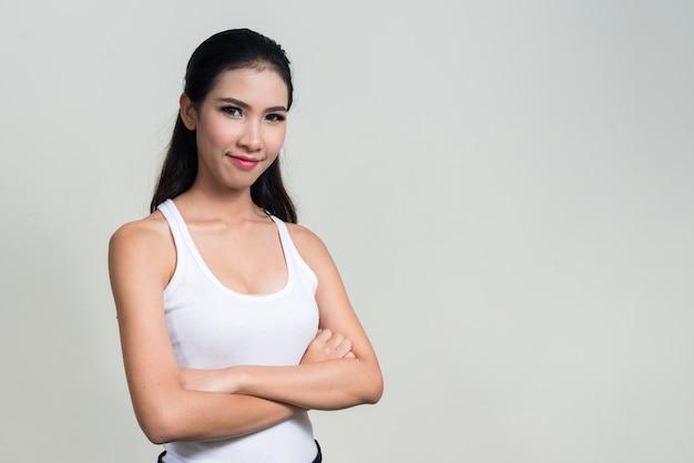 Jonge mooie aziatische vrouw klaar voor sportschool tegen witte ruimte