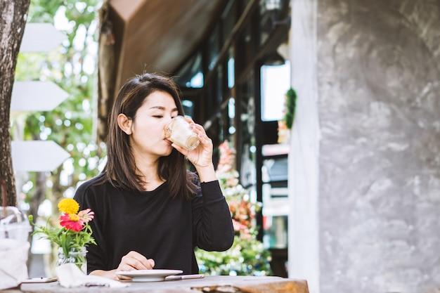Jonge mooie aziatische vrouw koffie drinken buitenshuis