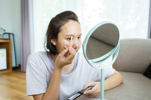Jonge mooie aziatische vrouw make-up vooraan een spiegel thuis toe te passen. cosmetica schilderen
