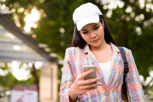 Jonge mooie aziatische vrouw met behulp van mobiele telefoon buitenshuis