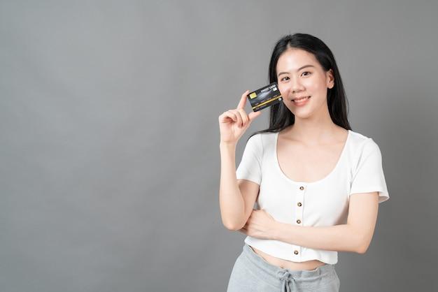 Jonge mooie aziatische vrouw met blij gezicht en presentatie van creditcard in de hand die vertrouwen en vertrouwen toont voor het doen van betaling