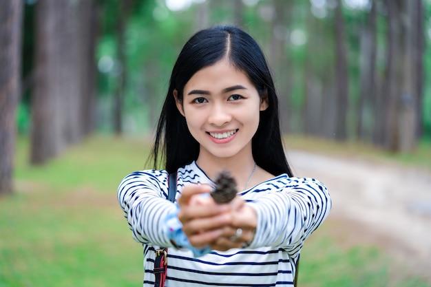 Jonge mooie aziatische vrouw met dennenzaad op dennenbos.