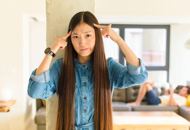 Jonge mooie aziatische vrouw met een serieuze en geconcentreerde blik, die brainstormt en nadenkt over een uitdagend probleem