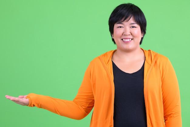 Jonge mooie aziatische vrouw met overgewicht klaar voor sportschool tegen chromakey met groene muur