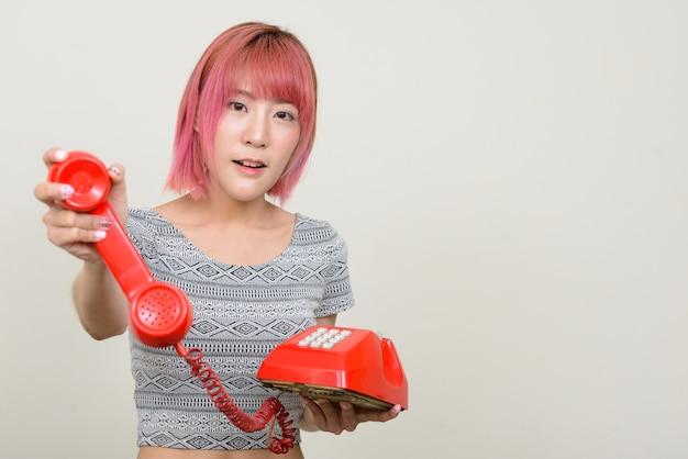 Jonge mooie aziatische vrouw met roze haren tegen witte muur