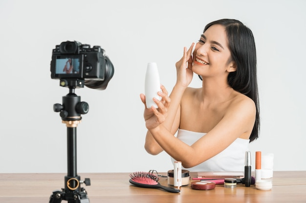 Jonge mooie aziatische vrouw professionele schoonheid vlogger of blogger opname make-up tutorial om te delen op sociale media over witte muur