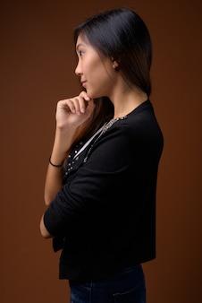 Jonge mooie aziatische vrouw tegen bruine achtergrond